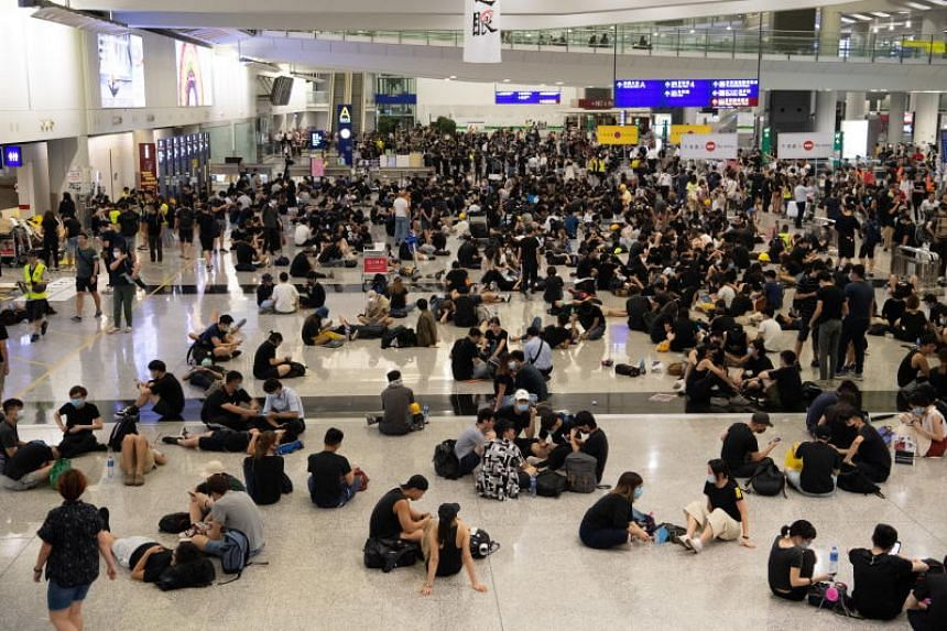 Thousands of protesters fill the arrivals and departures halls at Hong Kong International Airport on Aug 12, 2019.