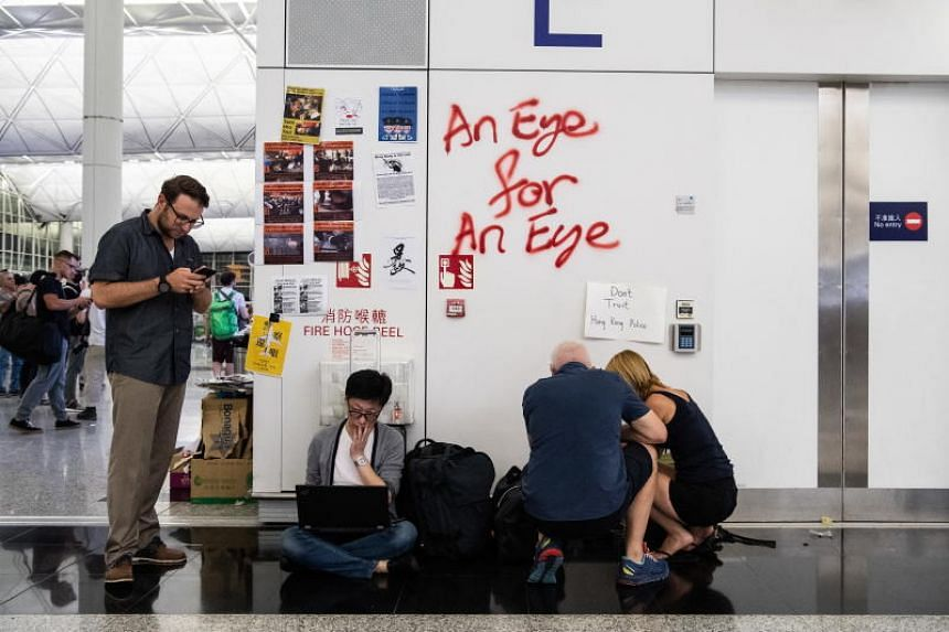Passengers wait as protesters occupy the Hong Kong International Airport on Aug 12, 2019.