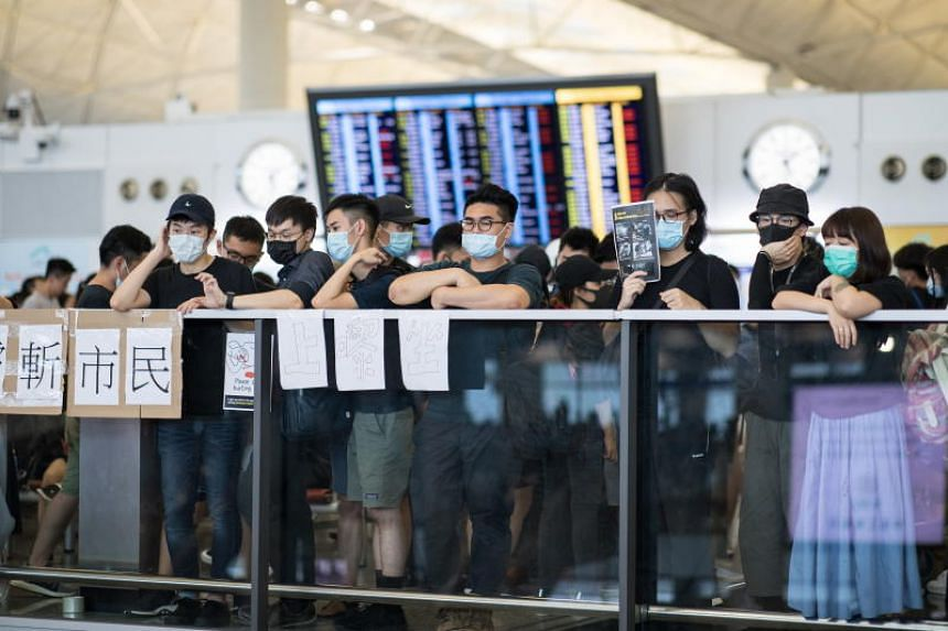 Pro-democracy protesters gather during a demonstration against police brutality and the controversial extradition bill at Hong Kong's international airport on Aug 12, 2019.