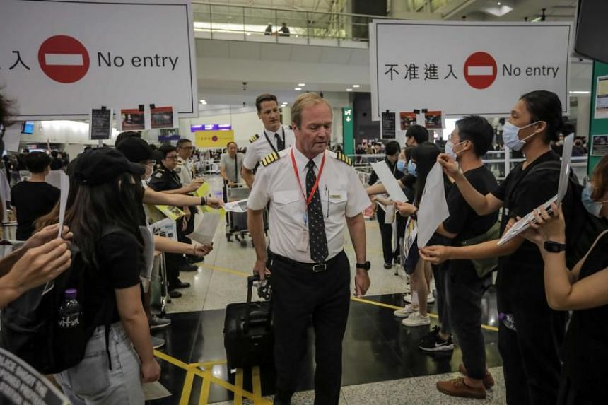 Hong Kong protesters greet the crew from one of the last few arriving flights at the city's international airport on Aug 12, 2019.  All flights departing Hong Kong in the afternoon of Aug 12 were cancelled.
