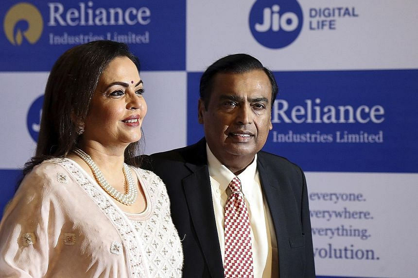 Reliance Industries chairman Mukesh Ambani, with wife Neeta, at the company's annual general meeting in Mumbai yesterday. The businessman said the company has agreed to sell a 20 per cent stake in its oil refinery and chemical unit to Saudi Aramco in
