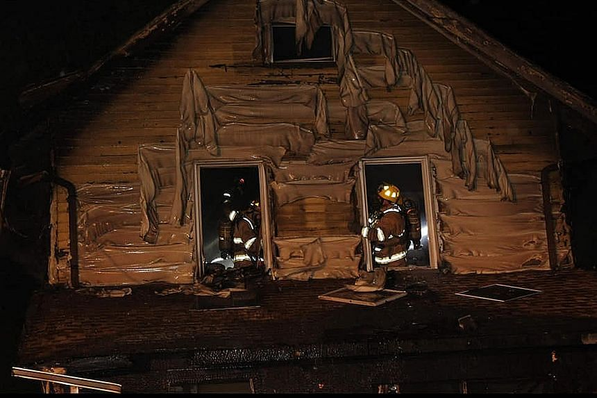 "Firefighters at the daycare centre in Erie, Pennsylvania, on Sunday. The US city's fire chief said the five children, aged eight months to seven years, were sleeping in second-floor bedrooms when the blaze broke out. He said investigators were ""leani"