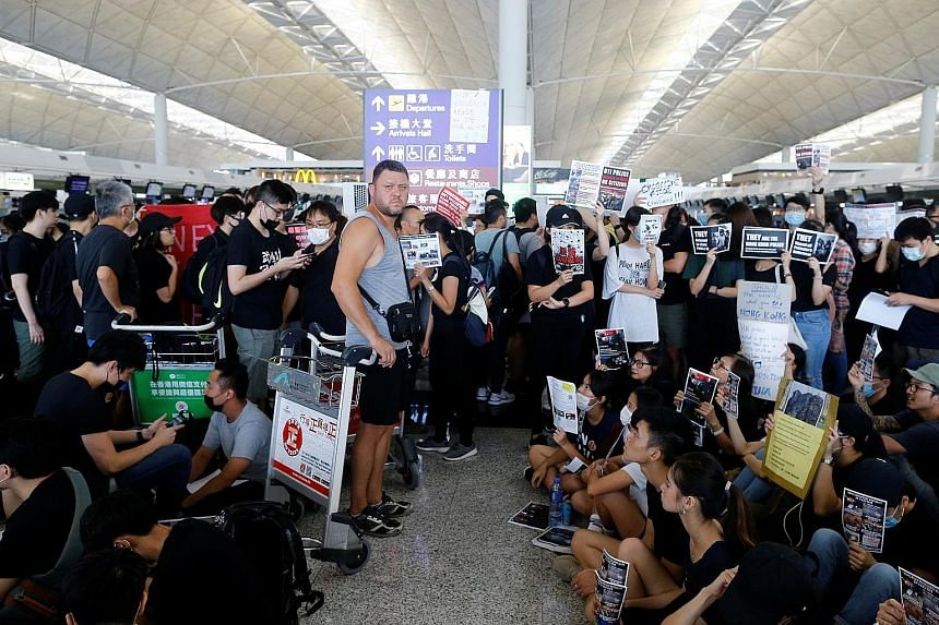 Above: Travellers gathering at the closed check-in counters as they waited for updates. Left: Protesters walking on a highway near the airport as public transport options, including the express train into the city, bus station and taxi stands, were i