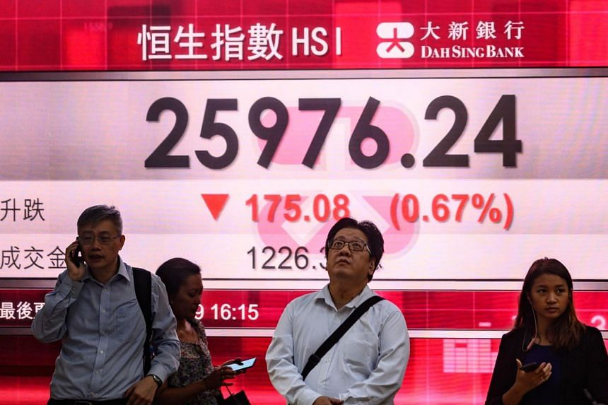 In a picture taken on Aug 6, 2019, pedestrians stand in front of a stocks display board showing the Hang Seng index at 25976.24, down 0.67 per cent, in Hong Kong.