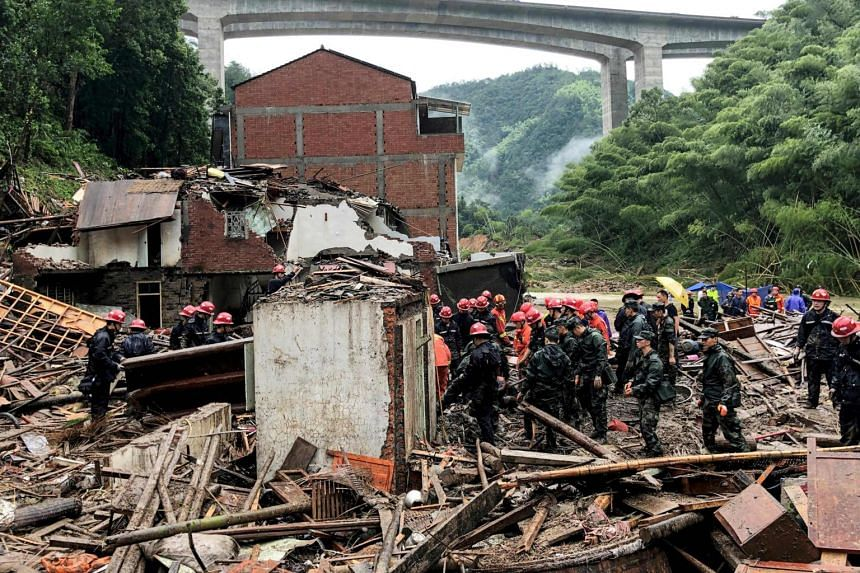 In a photo taken on Aug 11, 2019, rescuers and paramilitary police officers search in the rubble of damaged buildings after torrential rain caused by Typhoon Lekima in China's eastern Zhejiang province.