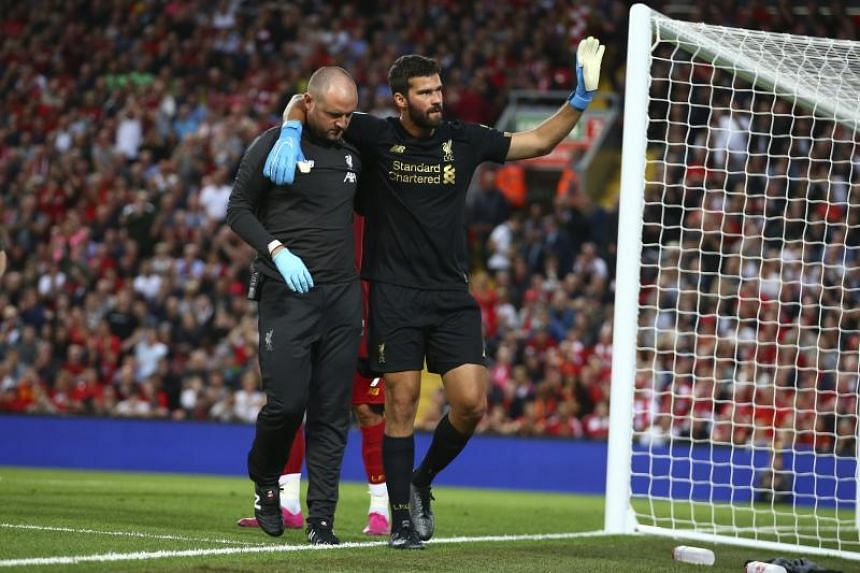 Liverpool's goalkeeper Alisson Becker waves to the fans as he leaves the pitch after an injury during the English Premier League soccer match between Liverpool and Norwich City at Anfield in Liverpool, on Aug 9, 2019.