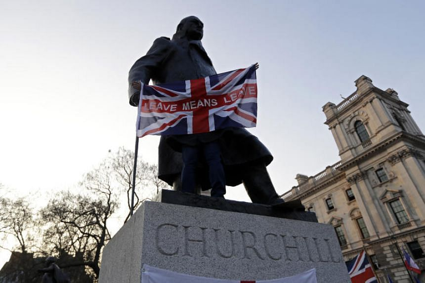 """In this photo taken on March 29, 2019, a pro-Brexit demonstrator holds a British flag with the words """"Leave Means Leave"""" in front of the Winston Churchill statue in London."""