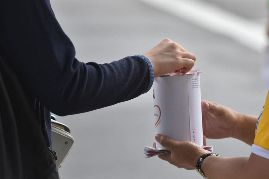 A member of the public donates money into flag day tin can at Yishun bus interchange on Feb 11, 2019.