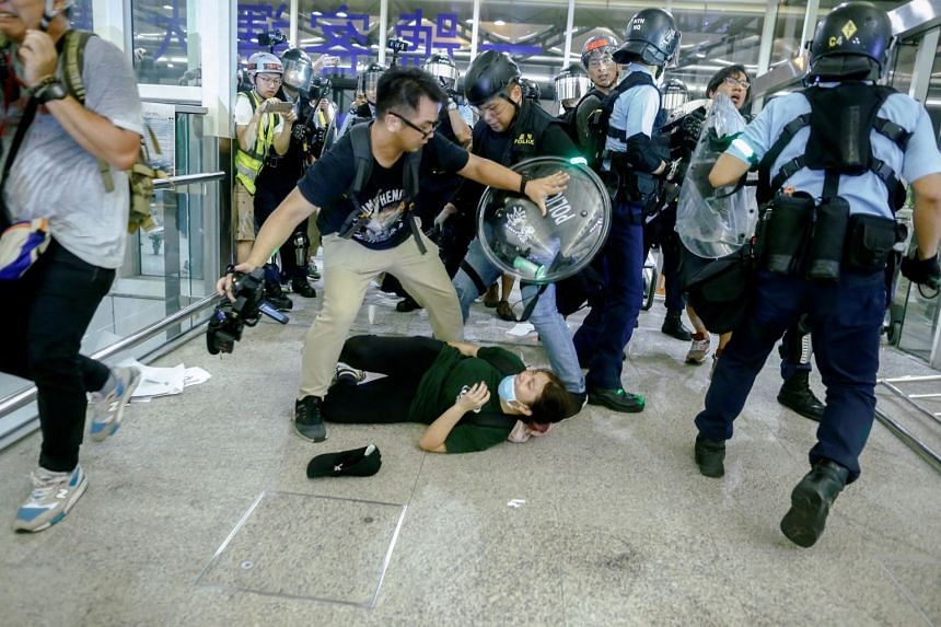Riot police use pepper spray to disperse anti-extradition bill protesters during a mass demonstration at the Hong Kong international airport, in Hong Kong on Aug 13, 2019.