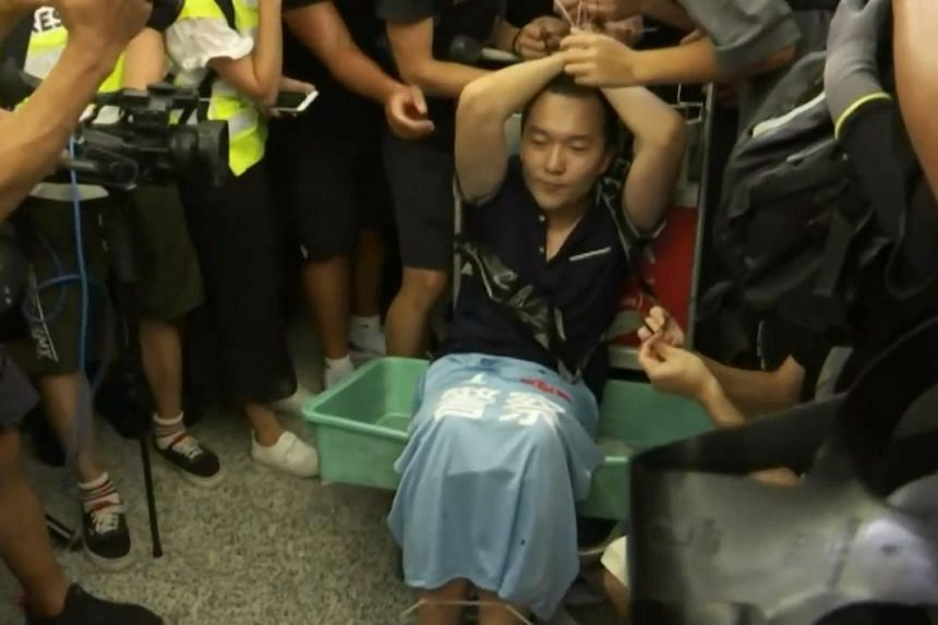 A suspected undercover policeman being restrained by protesters at the Hong Kong airport on Aug 13, 2019.