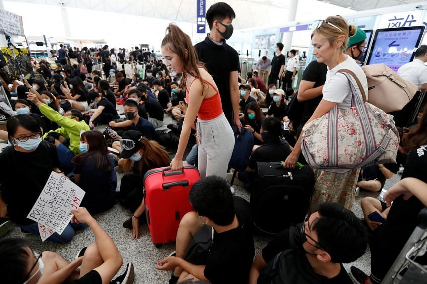 Passengers making their way through protesters during a demonstration at the Hong Kong airport on Aug 13, 2019.