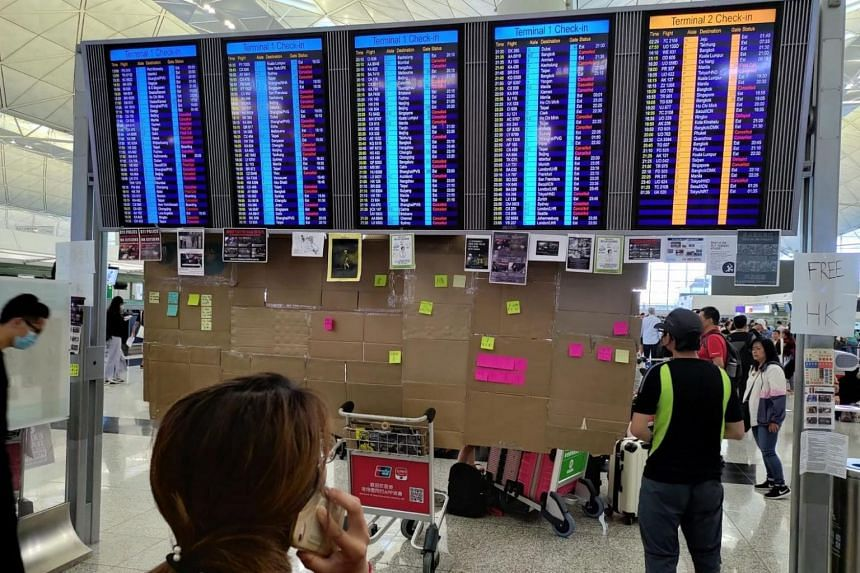 People reading the flight status board at the Hong Kong airport after the airport announced the suspension of all flight check-ins.