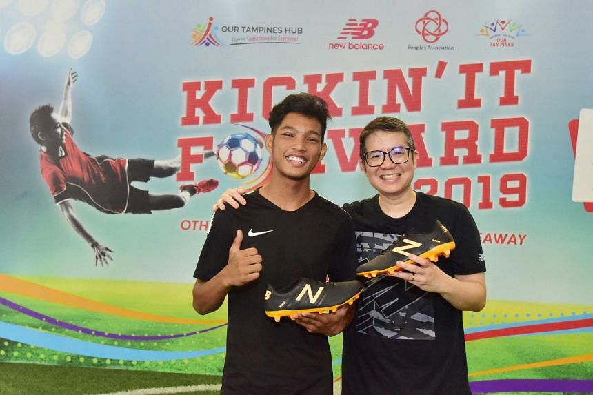 Alif Shafiq Sallim, one of the 150 young recipients of the New Balance futsal boots, with New Balance Country Manager Eugene Yeo at Our Tampines Hub on Aug 13, 2019.