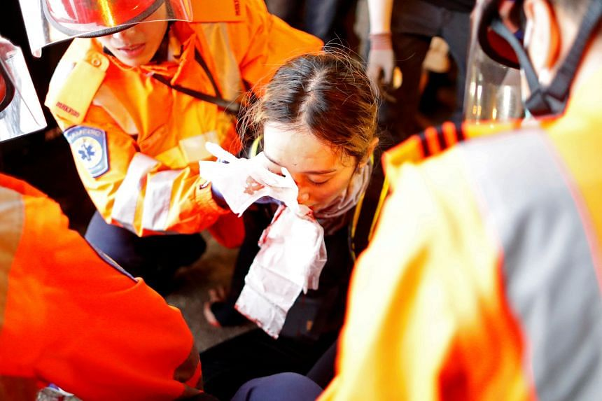 An injured young woman receiving medical aid after being hit by a pellet round in the right eye during a demonstration in Tsim Sha Tsui