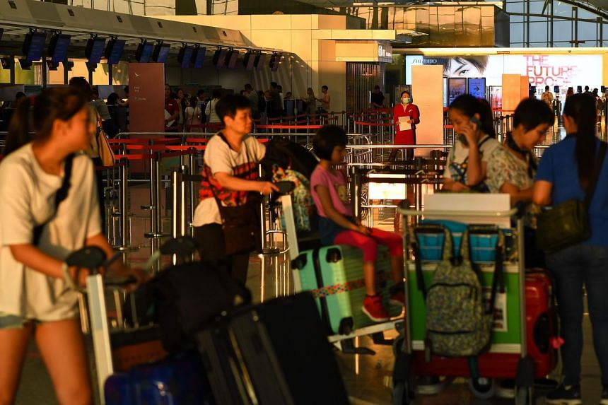 Passengers wait to check in after Hong Kong International Airport resumed operations on Aug 13, 2019.