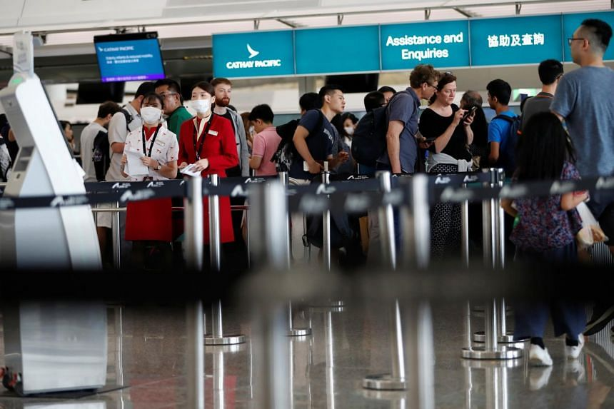 Passengers queue at Cathay Pacific's counters a day after the airport was closed due to a protest at Hong Kong International Airport on Aug 13, 2019.
