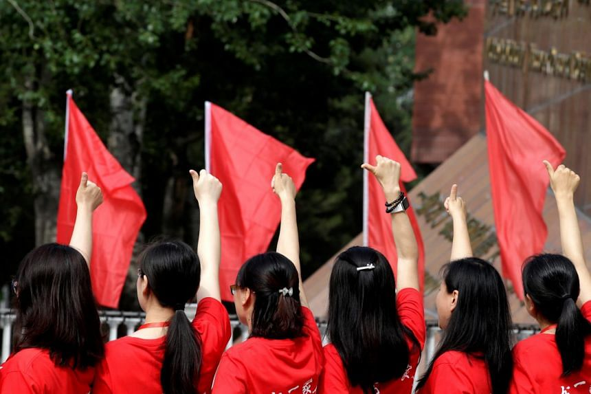 In a picture from on June 7, 2019, teachers cheer on the arrival of students at the High School affiliated to Renmin University of China for the first part of the country's annual national college entrance exam.