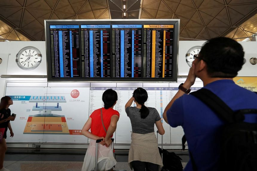 Passengers react as they check the flight information board at Hong Kong International Airport on Aug 13, 2019.