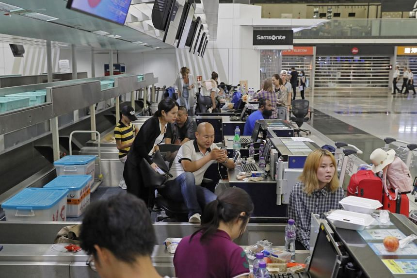 Stranded travellers sit in the check-in counters at the Hong Kong International Airport, on Aug 12, 2019.