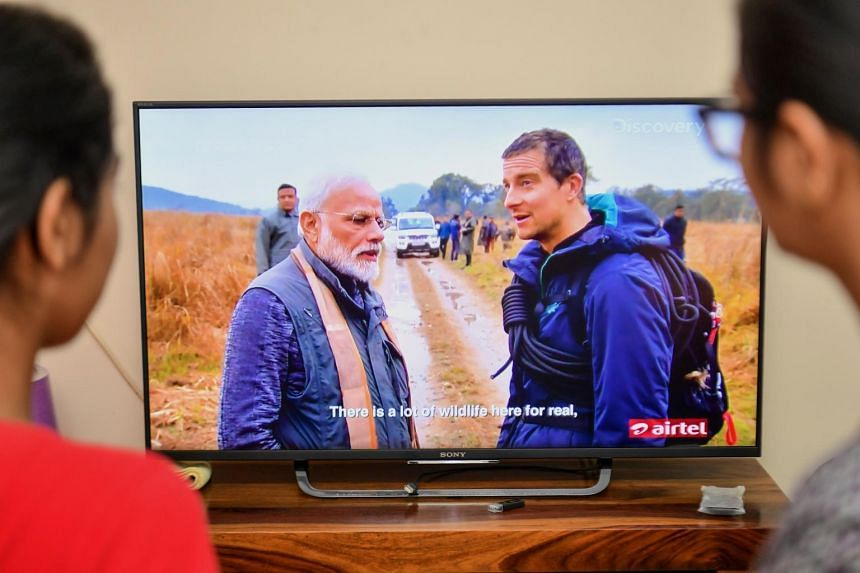 People watching the special edition of Man Vs Wild series hosted by survival expert Bear Grylls (right), going on a mission with Indian PM Narendra Modi, on Aug 12, 2019.