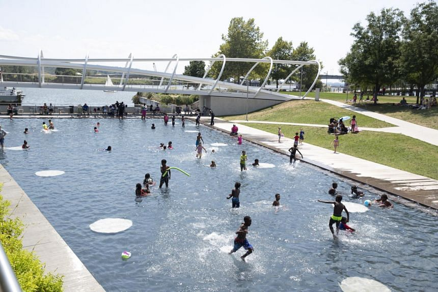 Children cooling off at Yards Park in Washington DC as temperatures reach 32.77 deg C, on Aug 12, 2019.
