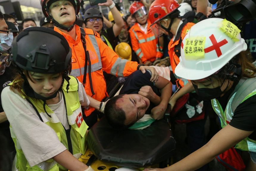An injured man whom protesters accused of being an undercover police officer is being taken by medical personal after clashes with anti-government protesters at Hong Kong's international airport.
