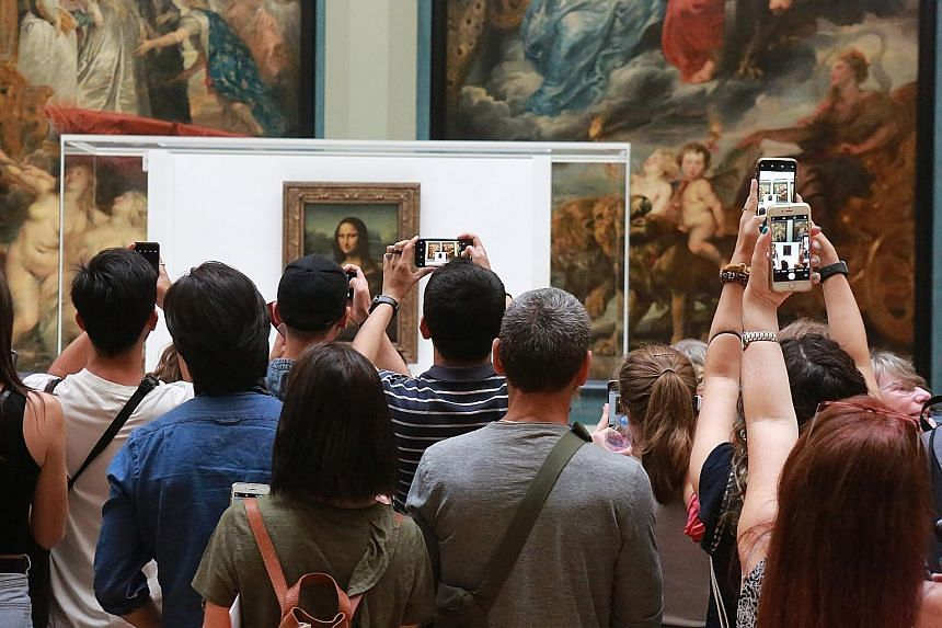 The Mona Lisa on display temporarily at the Louvre's Medici Gallery. Visitors have to view the 0.76m-tall painting from a distance of 4.6m. PHOTO: NYTIMES