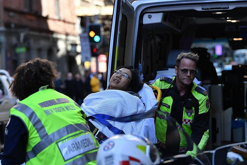 Far left: Sydney police detaining the attacker yesterday. Left: A woman was injured in the rampage and taken for emergency treatment.