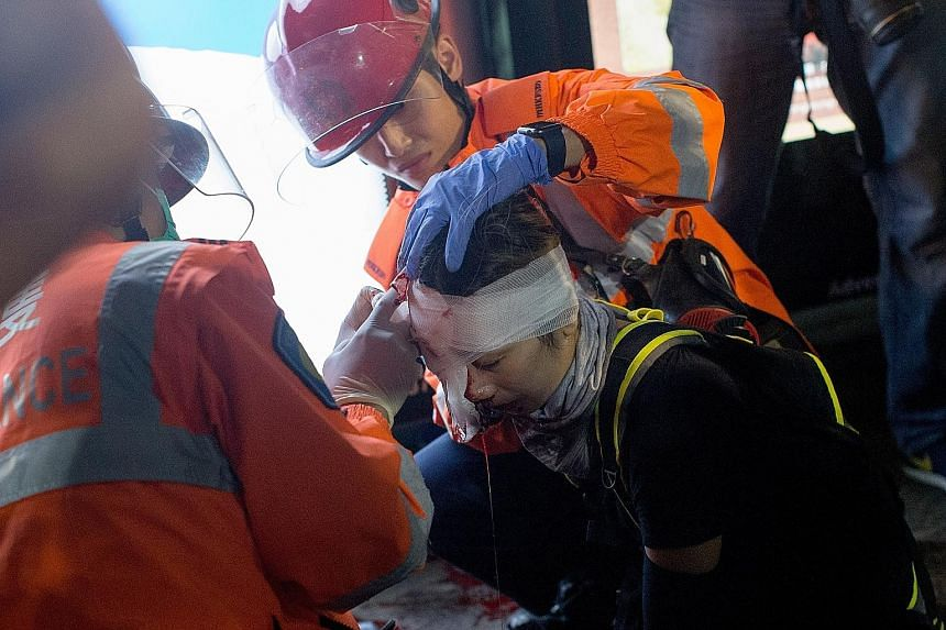 The injured woman being treated by medics in Tsim Sha Tsui in Hong Kong on Sunday. The police, who have been accused of causing the injury by firing a bean-bag round, said it was not clear what really happened. PHOTO:EPA-EFE A protester wearing an ey