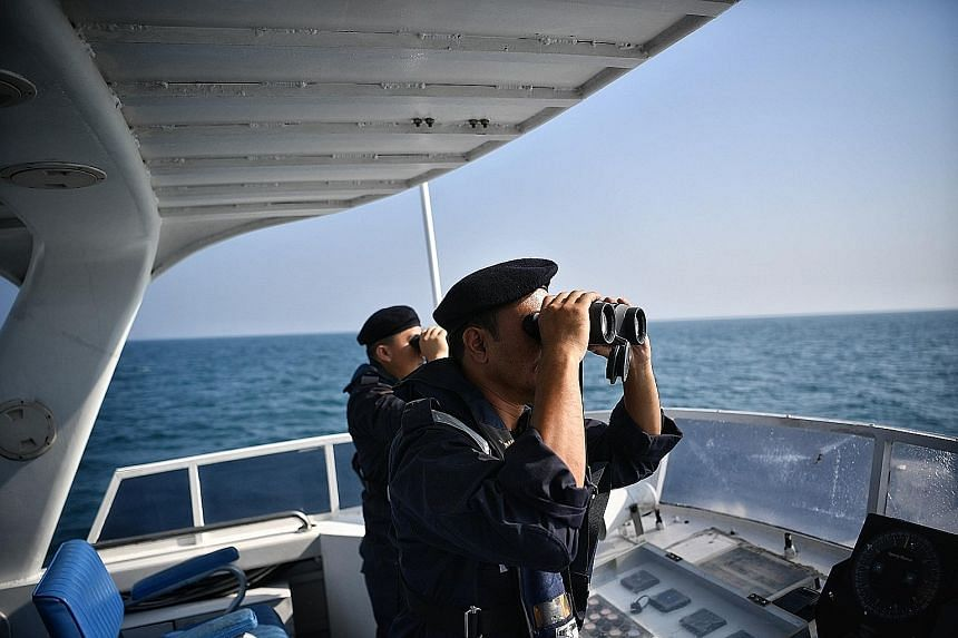 Rescuers from the Malaysian Maritime Enforcement Agency on a boat yesterday, scanning the sea with high-powered binoculars. ST PHOTO: ARIFFIN JAMAR