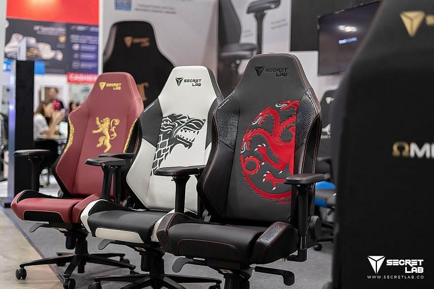 Secretlab's gaming chairs range from synthetic leather options for $429 to full leather designs for about $1,000. Secretlab founders Alaric Choo (wearing cap) and Ian Alexander Ang started the company in 2014, and its gaming chairs are now available