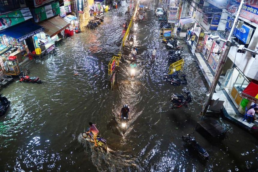 Commuters make their way through a flooded street after heavy rains in Allahabad on Aug 13, 2019. Heavy rains in parts of four Indian states have forced more than 1.2 million people to leave their homes, mostly for government-run relief camps.