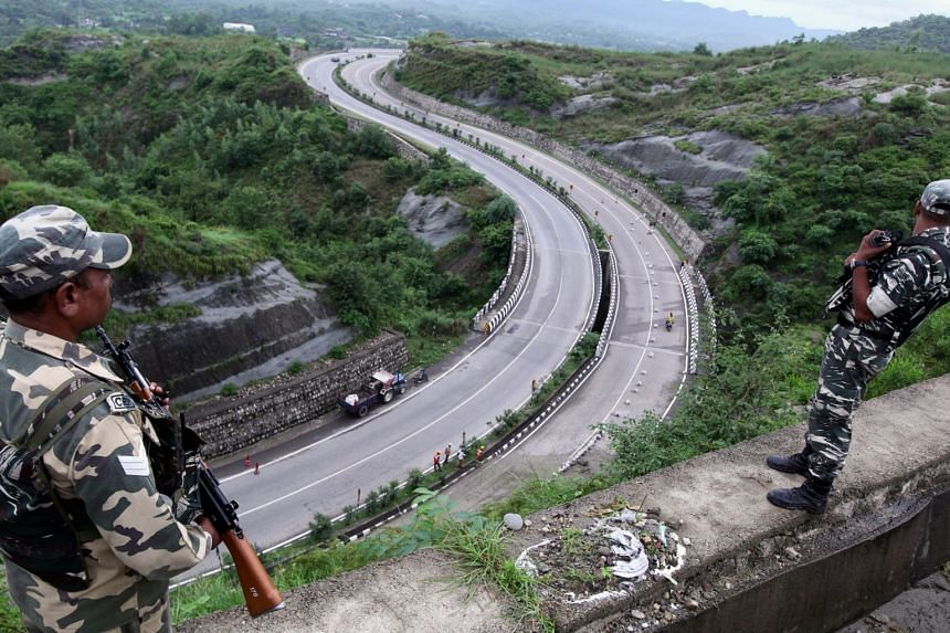 Indian security personnel stand guard overlooking the Jammu-Srinagar highway in Nagrota near Jammu on Aug 14, 2019.