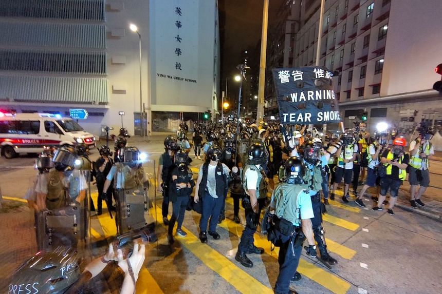 Police warn incoming traffic to clear the area at a road junction in Hong Kong's Sham Shui Po district on Aug 14, 2019.
