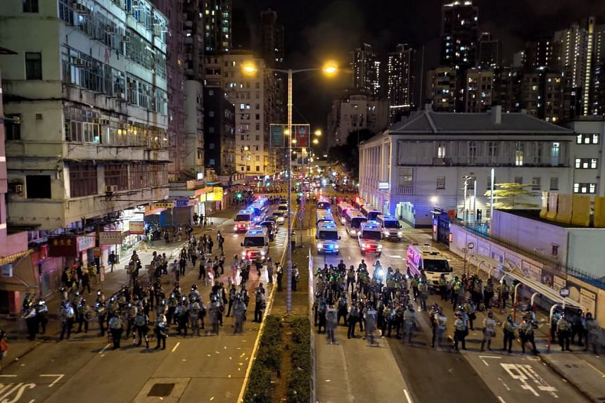 Riot police and vehicles assembled in front of Sham Shui Po police station at 10.10pm on Aug 14, 2019, after at least 20 rounds of tear gas were fired in the past hour to clear protesters.