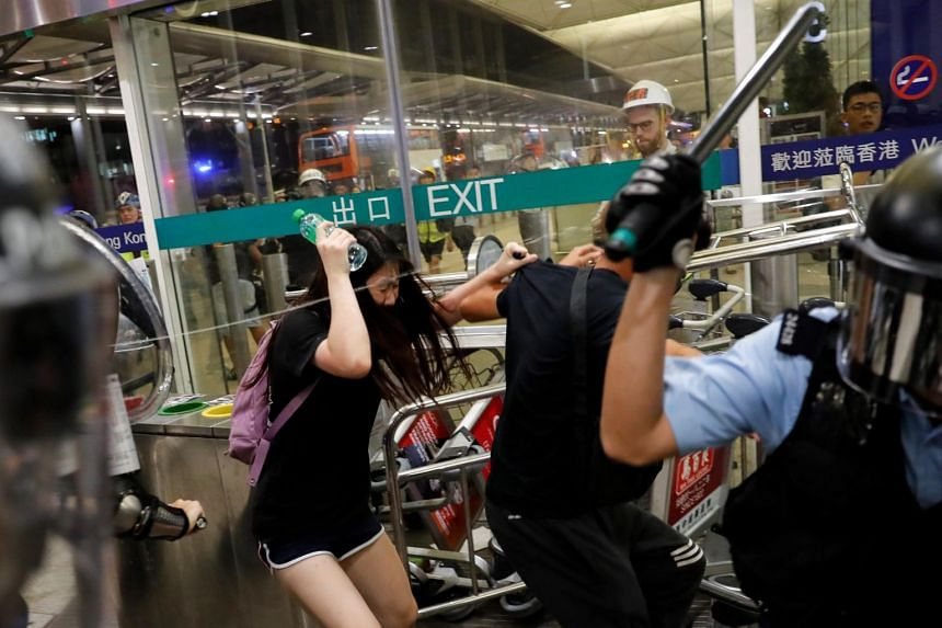Riot police use pepper spray to disperse anti-extradition bill protesters at the Hong Kong international airport on Aug 13, 2019.