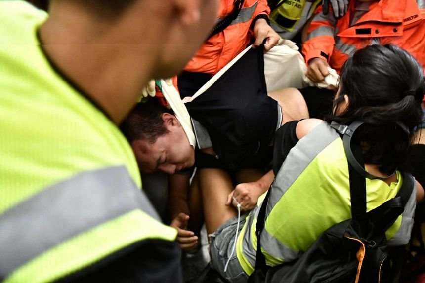 An injured man accused of being an undercover cop by Hong Kong protesters is taken away by paramedics at Hong Kong's international airport, late on Aug 13, 2019.