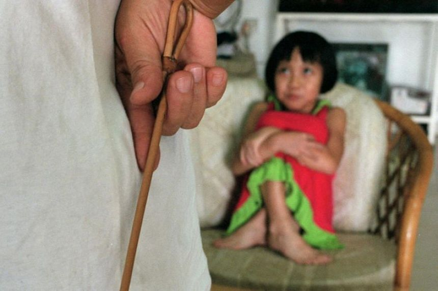 Posed photo of an adult holding a cane in front of a child.