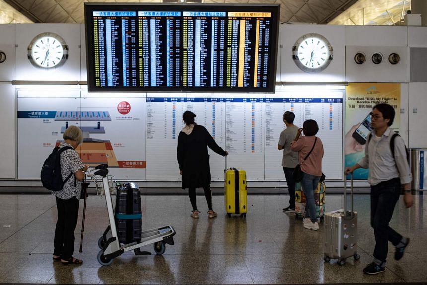 Passengers checking the status of their flights on an electronic board at Hong Kong's international airport, on Aug 14, 2019, following two days of protests.
