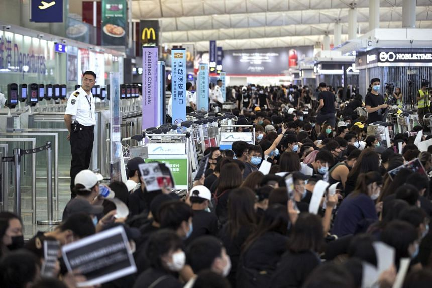 In a photo taken on Aug 13, 2019, airport security personnel look on as protesters use luggage trolleys to block the departure gates during a demonstration at the Airport in Hong Kong.