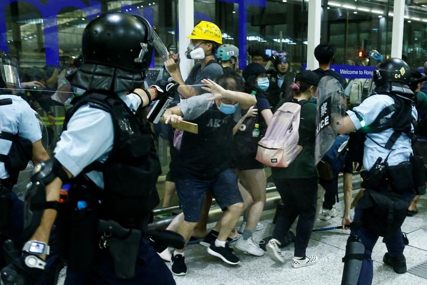 Police officers clash with anti-government protesters at Hong Kong International Airport, on Aug 13, 2019.
