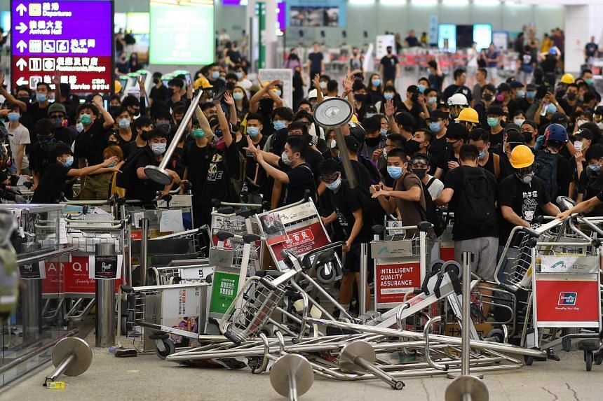 Pro-democracy protesters block the entrance to the airport terminals after a scuffle with police at Hong Kong's international airport on Aug 13, 2019.