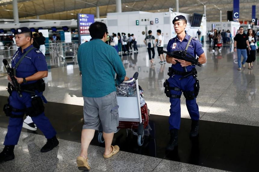 Armed police patrol the departure hall of Hong Kong's international airport following two days of protests, on Aug 14, 2019.