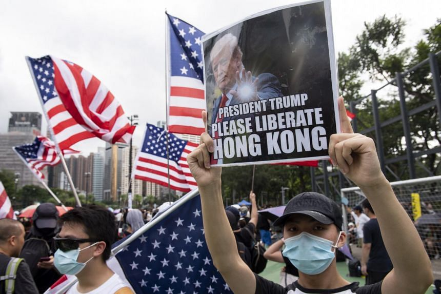 In a photo taken on Aug 11, 2019, anti-government protesters carry US national flags and placards that appeal to President Trump during a rally at Victoria Park in Hong Kong.