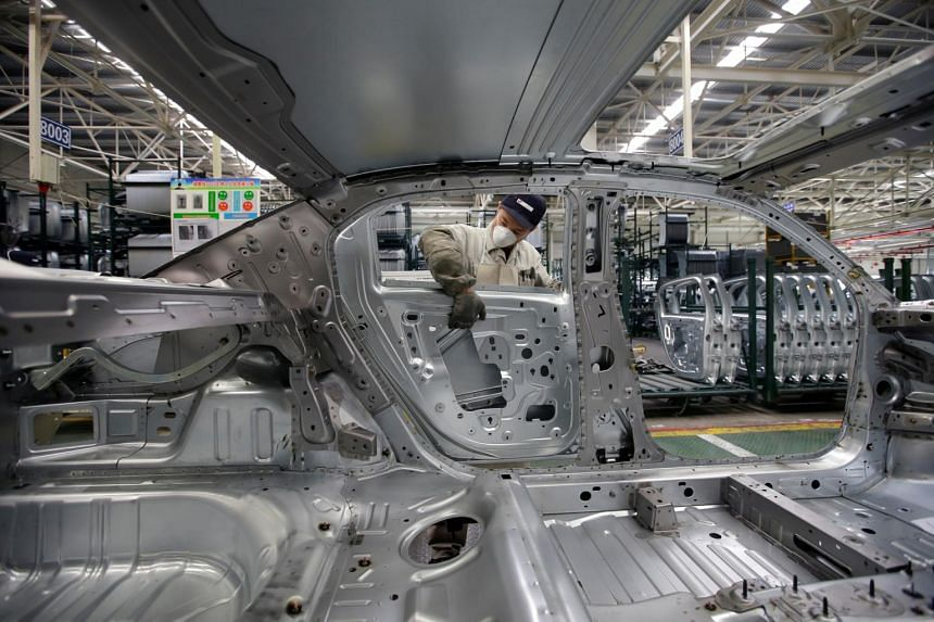 An employee installs car doors at a production line of Dongfeng Peugeot Citroen Automobile factory in Wuhan, Hubei province.