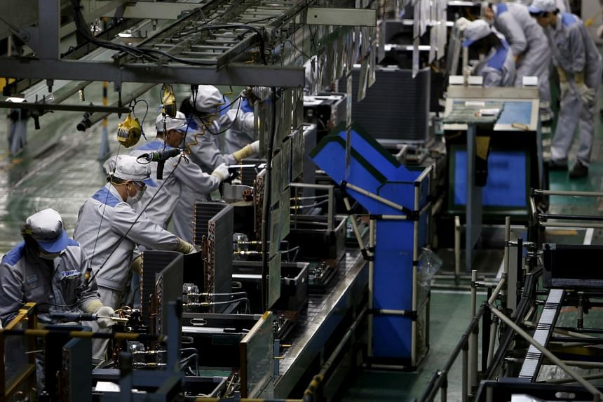 Employees working on a production line of air conditioning units in Shiga prefecture, western Japan.