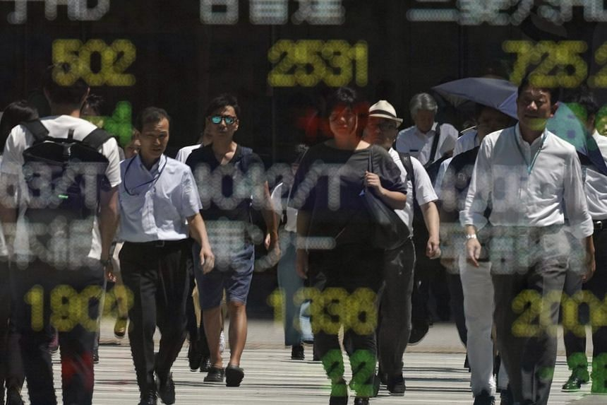 Pedestrians reflected in a stock market indicator board in Tokyo, Japan, on Aug 7, 2019.
