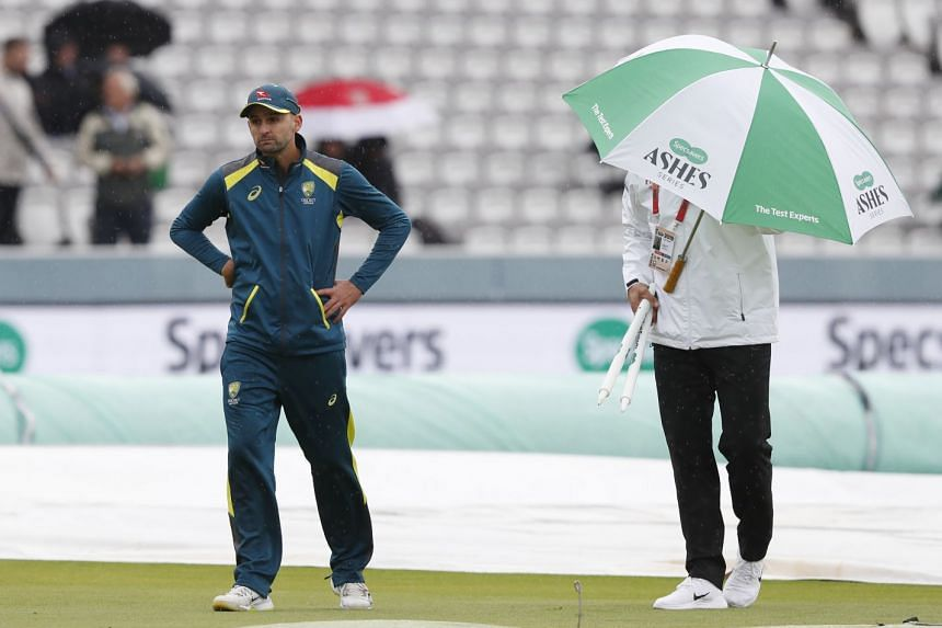 Australia's Nathan Lyon (left) walks off the pitch after speaking to 4th umpire Alex Wharf as rain delays play.