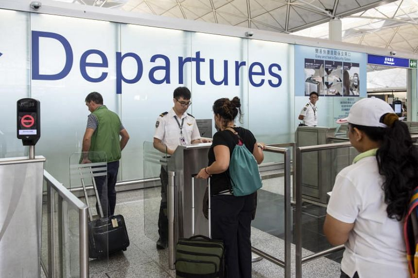 Passengers having their passports checked at departure gates in Hong Kong International Airport on Aug 14, 2019.