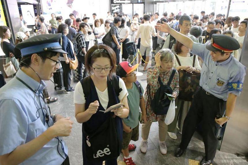 Railway employees assist stranded passengers at the Hakata Shinkansen station in the city of Fukuoka on Aug 14, 2019.
